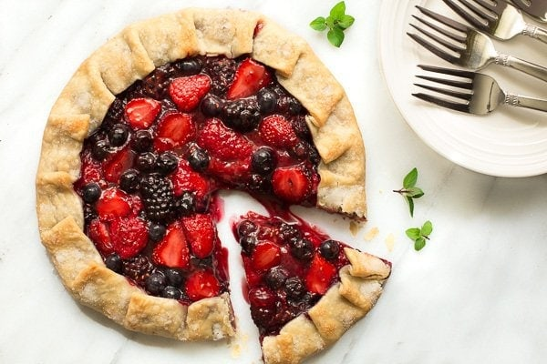 Overhead photo of a Ten Minute Summer Berry Galette on a marble slab with a slice pulled out and serving plates to the right.