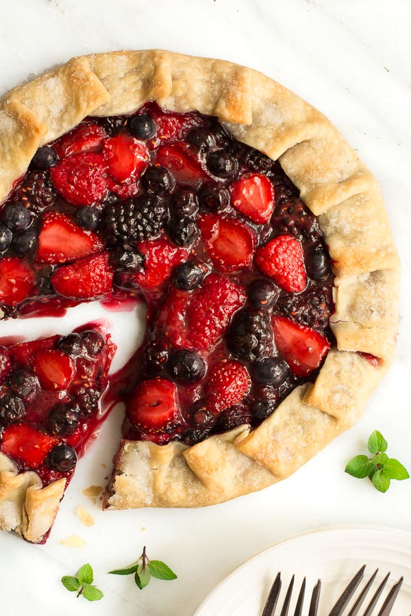 Overhead photo of a Summer Berry Galette on a marble slab with a slice pulled out.