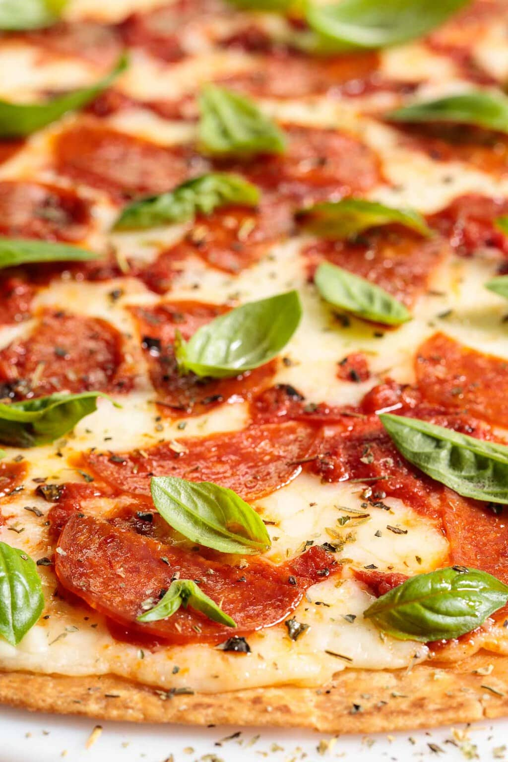 Closeup side photo of an Easy Thin Crust Pizza with basil and pepperoni.