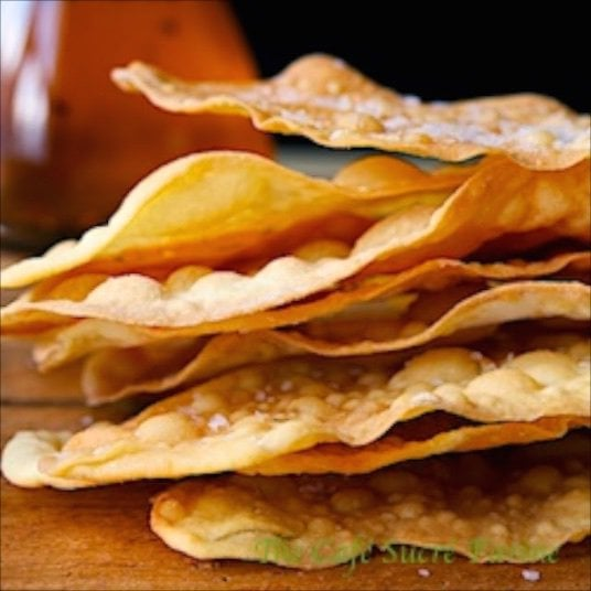 Closeup photo of a rustic stack of Chili Oil Rubbed Flatbread Crackers highlighting the thin, crisp edges. A glass cruet of chili oil is in the left background.