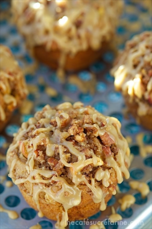 Vertical picture of caramel apple muffins on a cooling rack