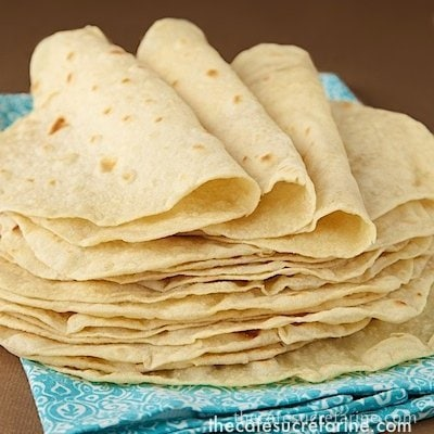 Photo of Best Ever Homemade Flour Tortillas on a turquoise napkin.