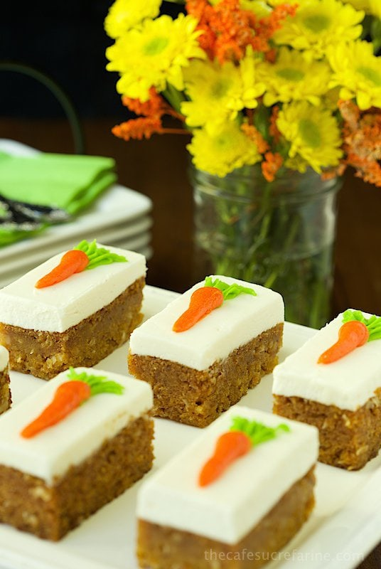 Vertical photo of Carrot Cake Bars on a white serving platter with yellow and orange flowers in the background.