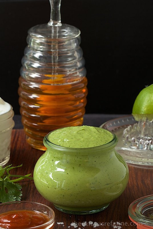 Photo of a jar of Avocado Crema with the ingredients for making it surrounding the jar.