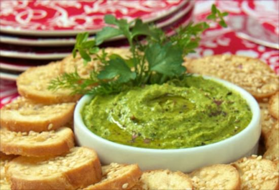 A horizontal photo of a bowl of Guacamole Hummus surrounded by red serving dishes and crostini bread.