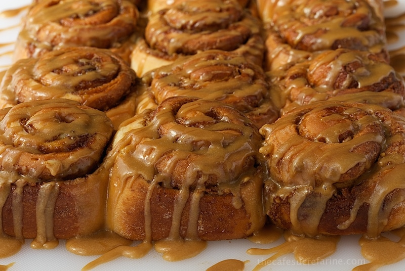 Photo of a row of Easy Cinnamon Rolls with Caramel Icing on a white breadboard.