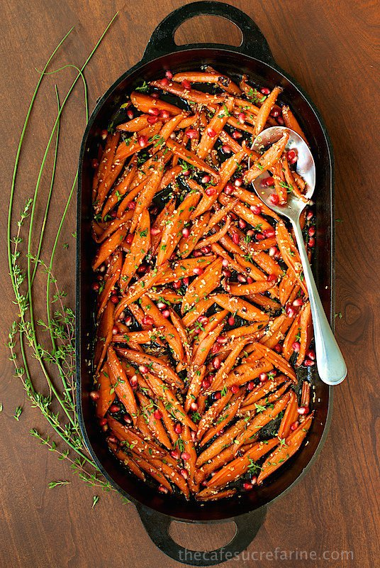 Overhead vertical photo of Honey Maple Roasted Carrots in an oval cast iron baking dish.