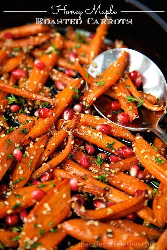 Closeup photo of a pan of Honey Maple Roasted Carrots with a silver spoon filled with carrots. A graphic title, Honey Maple Roasted Carrots is at the top of the photo.