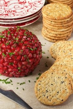 Vertical picture of Pomegranate, Parsley and Pecan Cheeseball with crackers