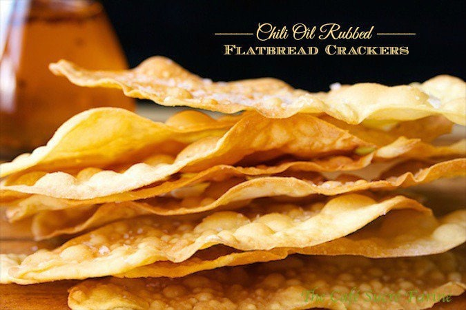 Closeup photo of a stack of Chili Oil Rubbed Flatbread Crackers, emphasizing the thin, rustic look of the crackers.