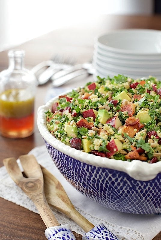 Vertical picture of quinoa and kale salad in a blue and white bowl with stacked plates and dressing in the background