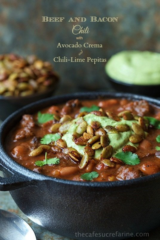 Photo of a cast iron pot of Beef and Bacon Chili with Avocado Crema and Chili-Lime Pepitas. A graphic title is at the top of the photo.