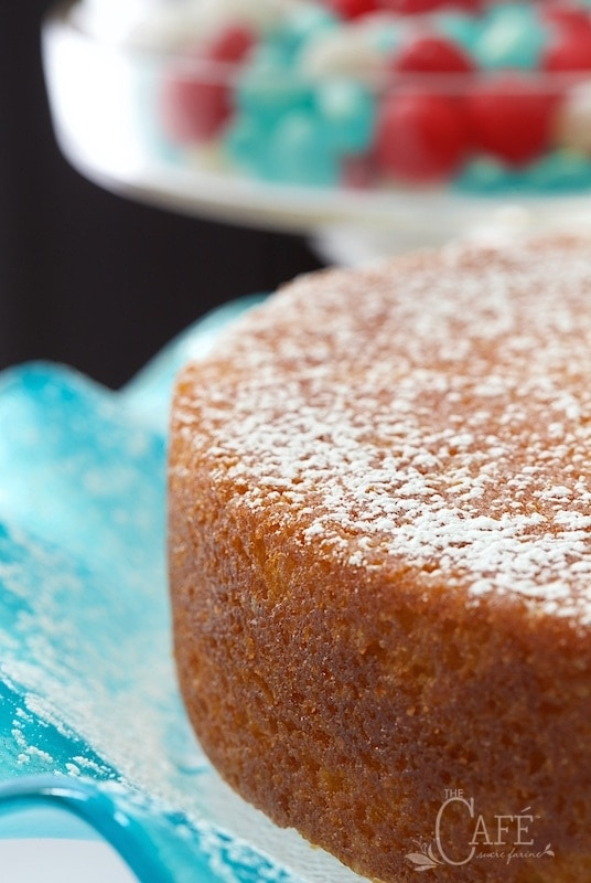 Vertical close up picture of french grandmothers lemon yogurt cake on a blue cake stand
