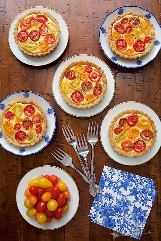 Overhead photo of Goat Cheese and Tomato Soufflé Tarts on blue and white patterned plates on a wooden table.