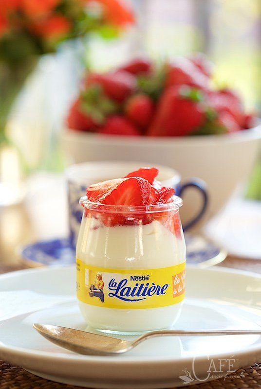 Shot of a Nestle La Laitiere yogurt jar on a table with a bowl of fresh strawberries in the background.