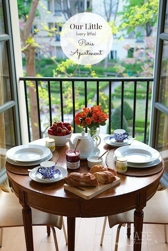 Shot of a breakfast table in front of a balcony window overlooking a Paris courtyard in full spring bloom.