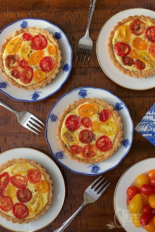 Overhead photo of blue and white patterned plates with Goat Cheese and Tomato Tarts.