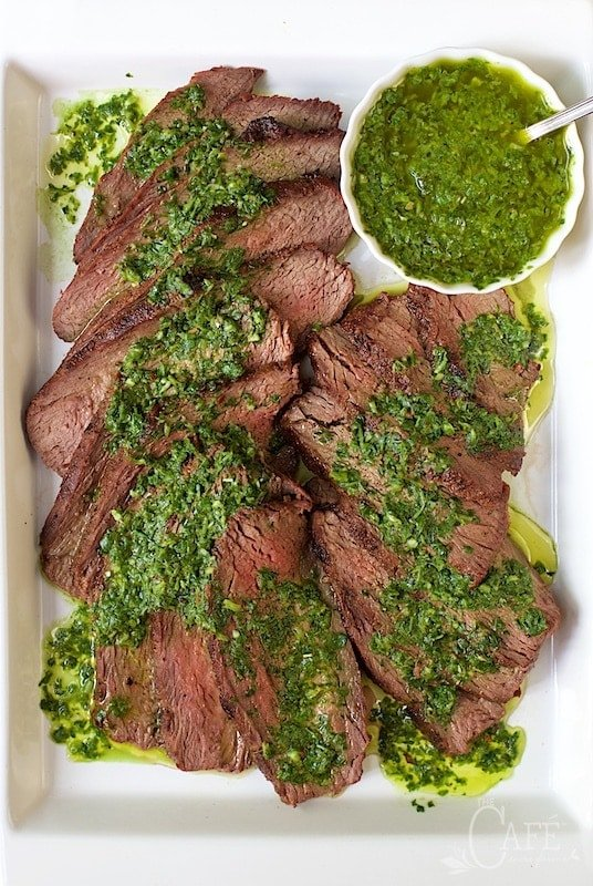 Vertical image of Grilled Tri-Tip with Chimichurri Sauce on a white rectangular platter.