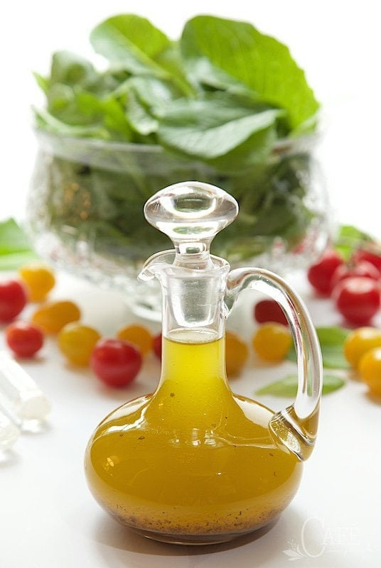 Vertical photo of Zoe's Copycat Salad Dressing in a glass cruet with fresh cherry tomatoes and greens in the background.
