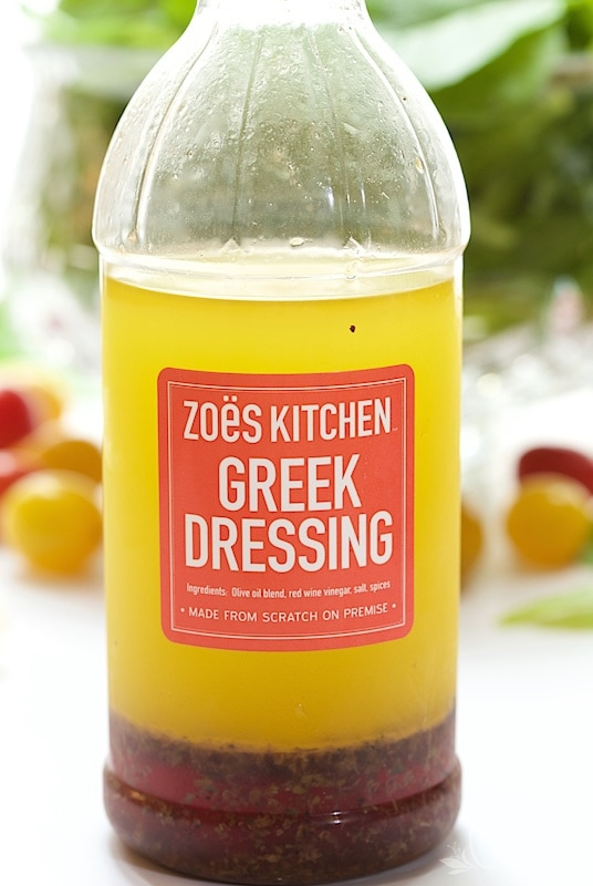 A vertical image of an authentic bottle of Zoe's Kitchen's Greek Dressing, the inspiration for Zoe's Copycat Salad Dressing.