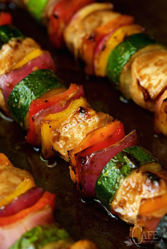 Closeup of Asian Barbecued Chicken and Veggie Skewers on a metal sheet in a diagonal pattern.