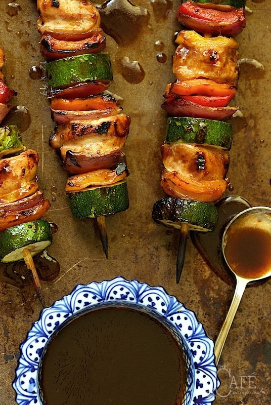 Overhead photo of Asian Barbecued Chicken and Veggie Skewers on a metal sheet with a dish of dipping sauce at the bottom of the photo.