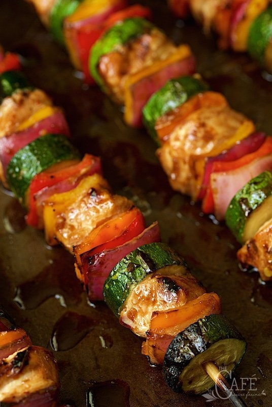 Closeup photo of rows of Asian Barbecued Chicken and Veggie Skewers on a metal pan.