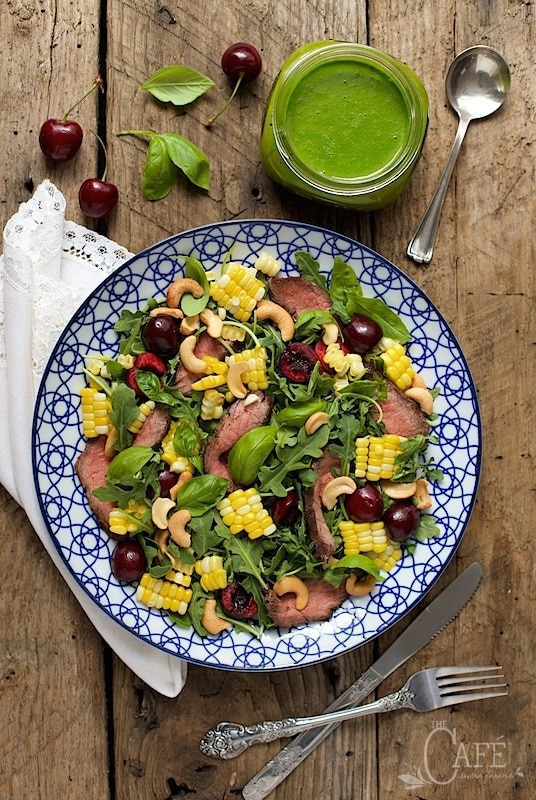 Overhead picture of Grilled Steak Salad with Sweet Cherries and Ginger Basil Dressing on a wooden table