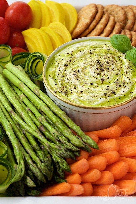 Close up picture of Lemon Tahini Dip with Crudites surrounded with an assortment of appetizer veggies and crackers.