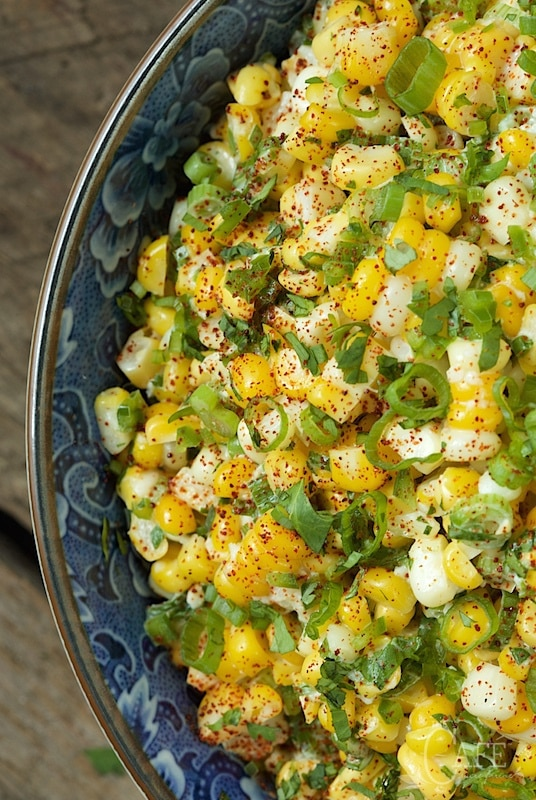 Overhead closeup photo of a blue bowl filled with Mexican Street Corn - Esquites.