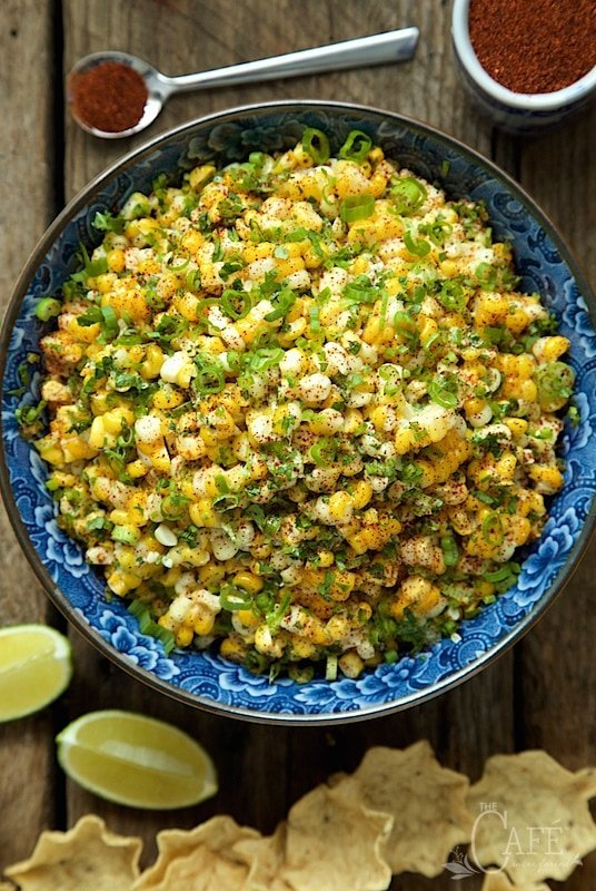 Overhead photo of a bowl of Mexican Street Corn - Esquites on a barnboard table with chips, lime wedges and a bowl of chili powder.