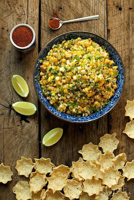 Overhead photo of a blue bowl filled with Mexican Street Corn - Esquites on a barn board table with chips, lime wedges and a dish of chili powder.
