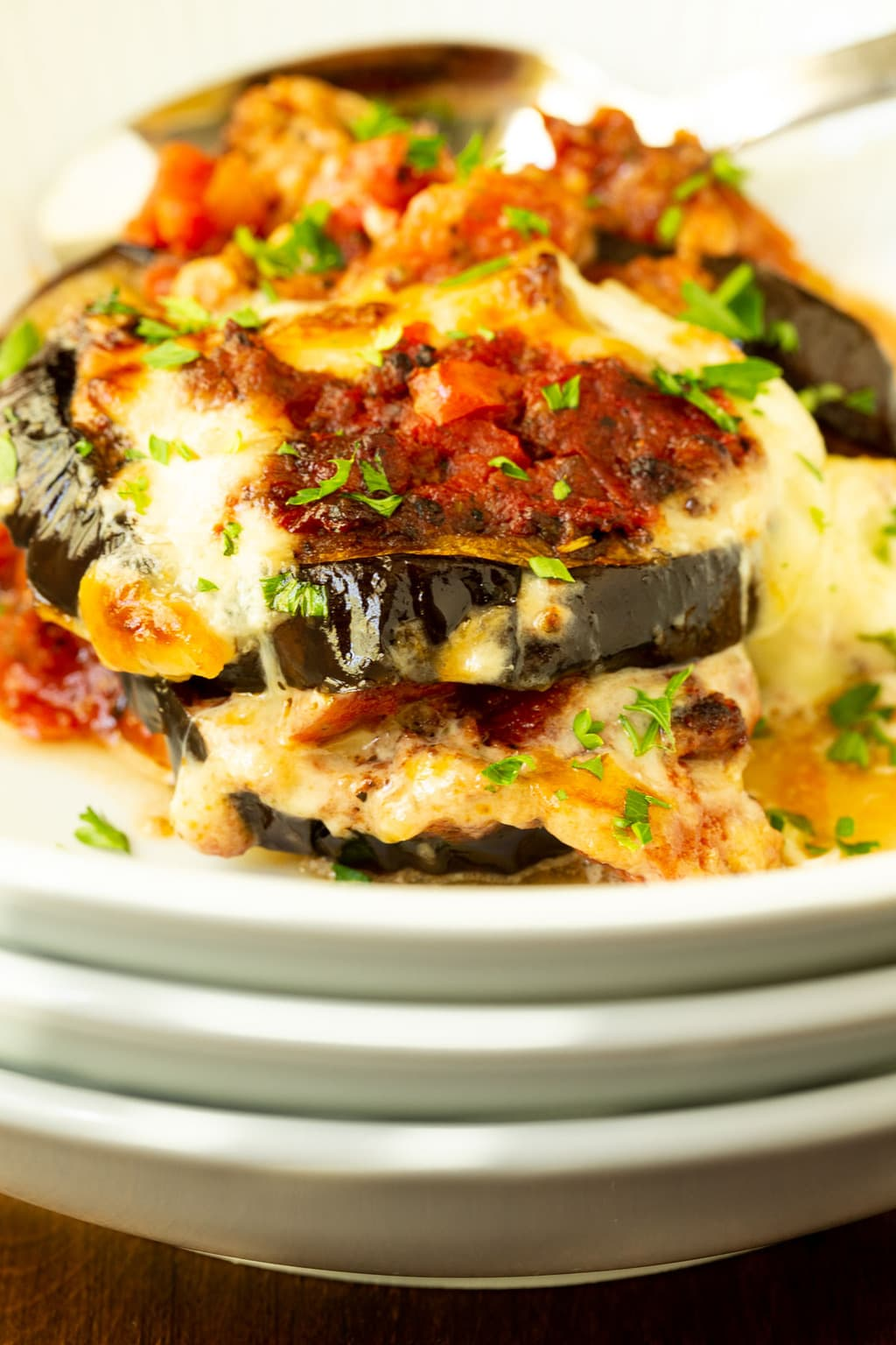 Vertical extreme closeup photo of a serving of Eggplant Italian Sausage Gratin in a white individual serving bowl.