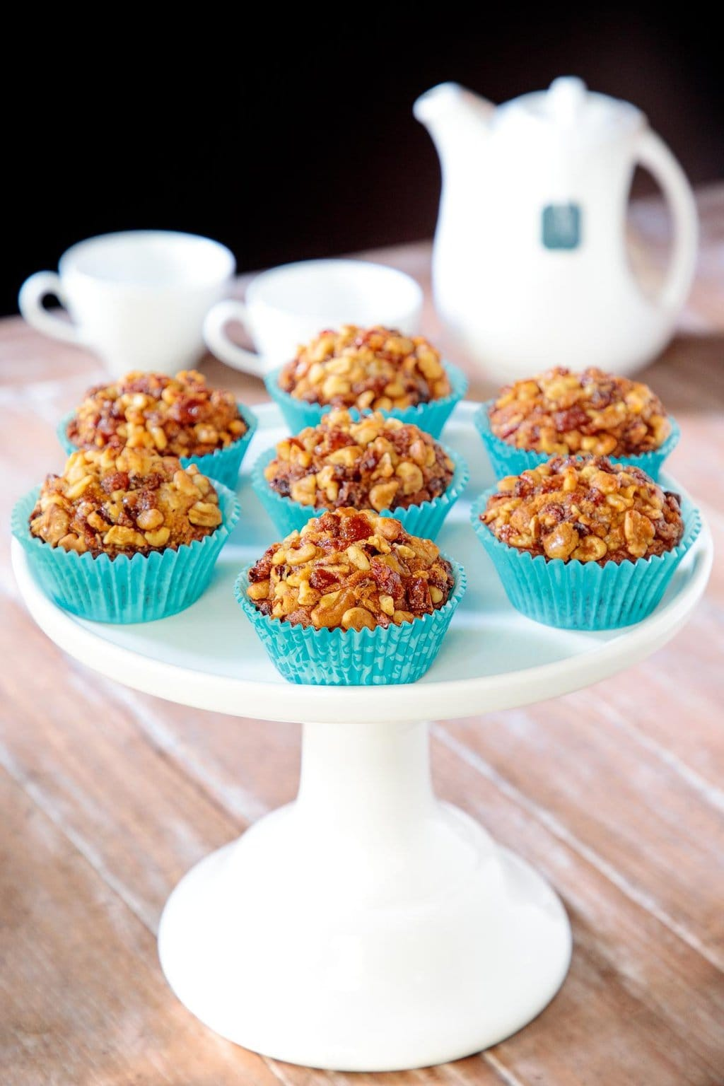 Vertical photo of a batch of Candied Walnut Date Banana Muffins in turquoise cupcake liners on a white pedestal serving plate.