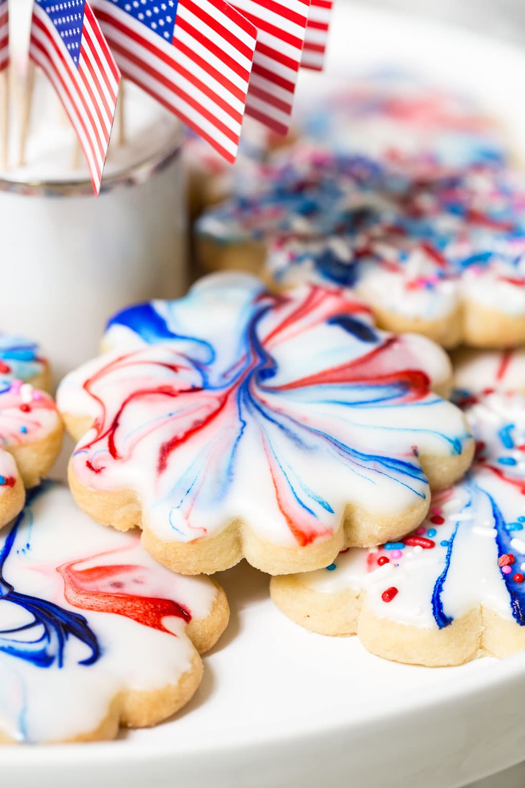 Vertical closeup photo of a batch of Red, White, and Blue Glazed Shortbread Cookies.