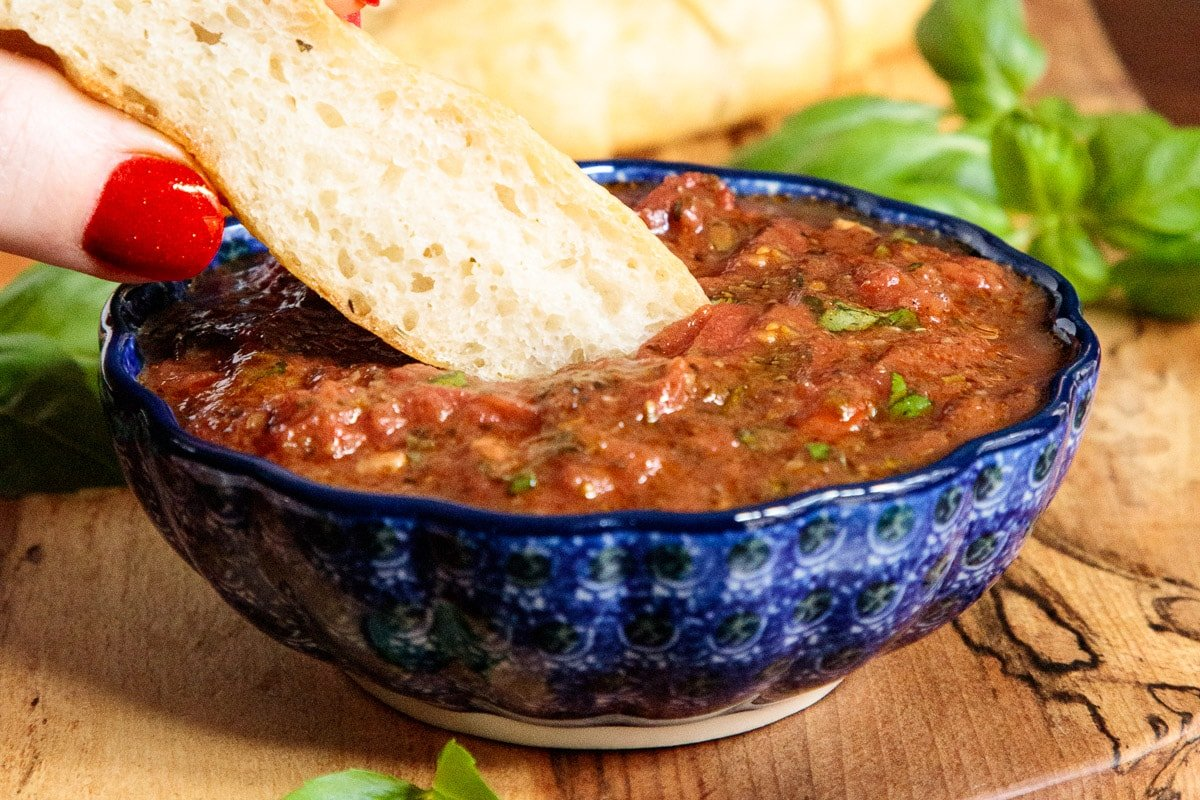 Horizontal closeup photo of a blue patterned bowl of Quick and Easy Marinara Sauce with a slice of bread being dipped into it.