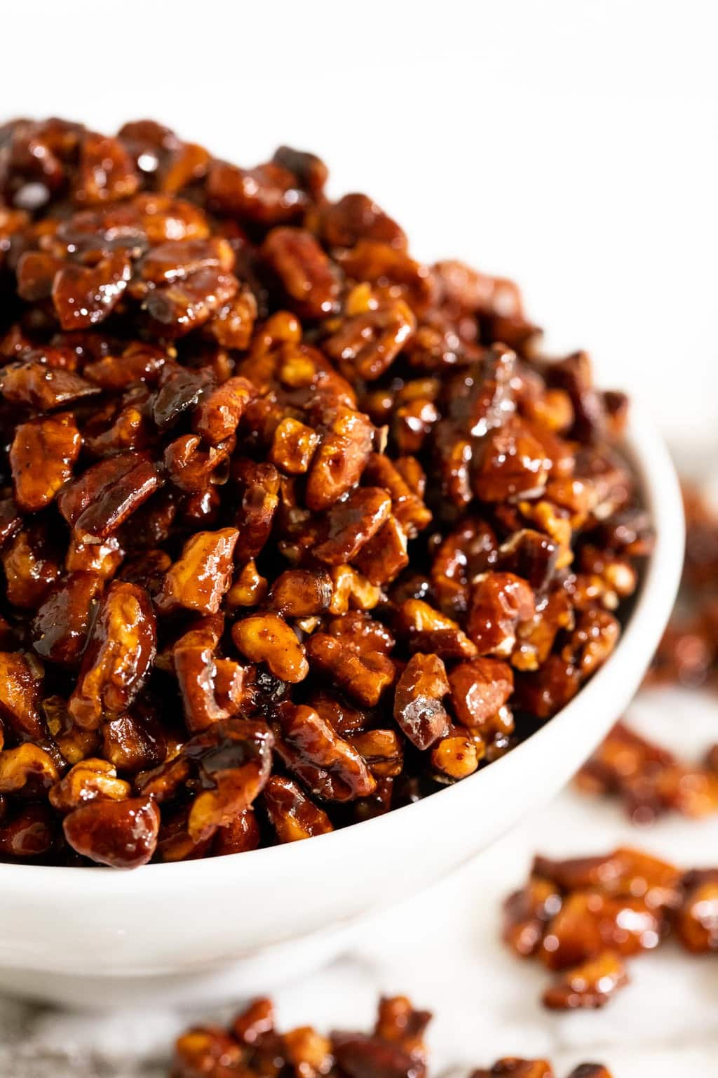 Vertical extreme closeup photo of a bowl of Easy Candied Pecans.