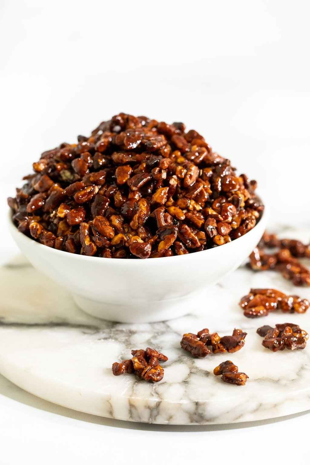 Vertical photo of a white serving bowl of Easy Candied Pecans using chopped pecans on a round marble slab.