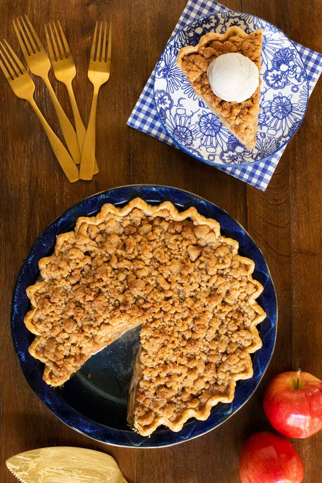Vertical overhead photo of Annie's Easy Apple Crumble Pie on a wooden table with apples, forks and napkins