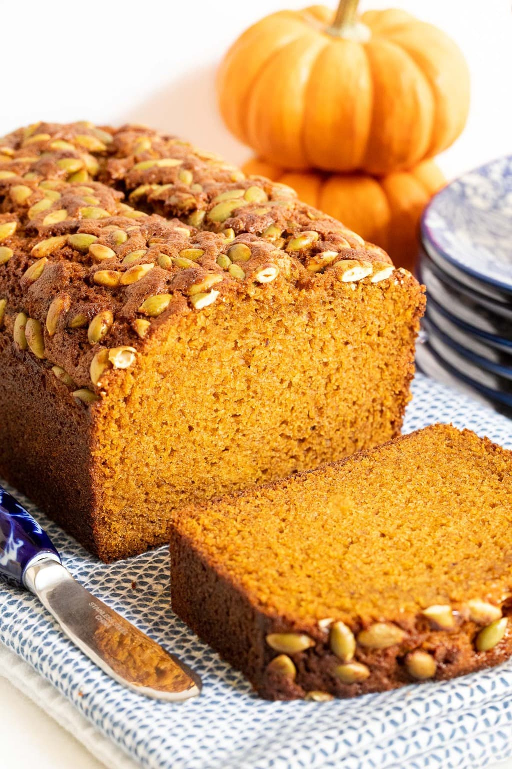 Vertical close up picture of Pumpkin Bread topped with pepitas and sliced