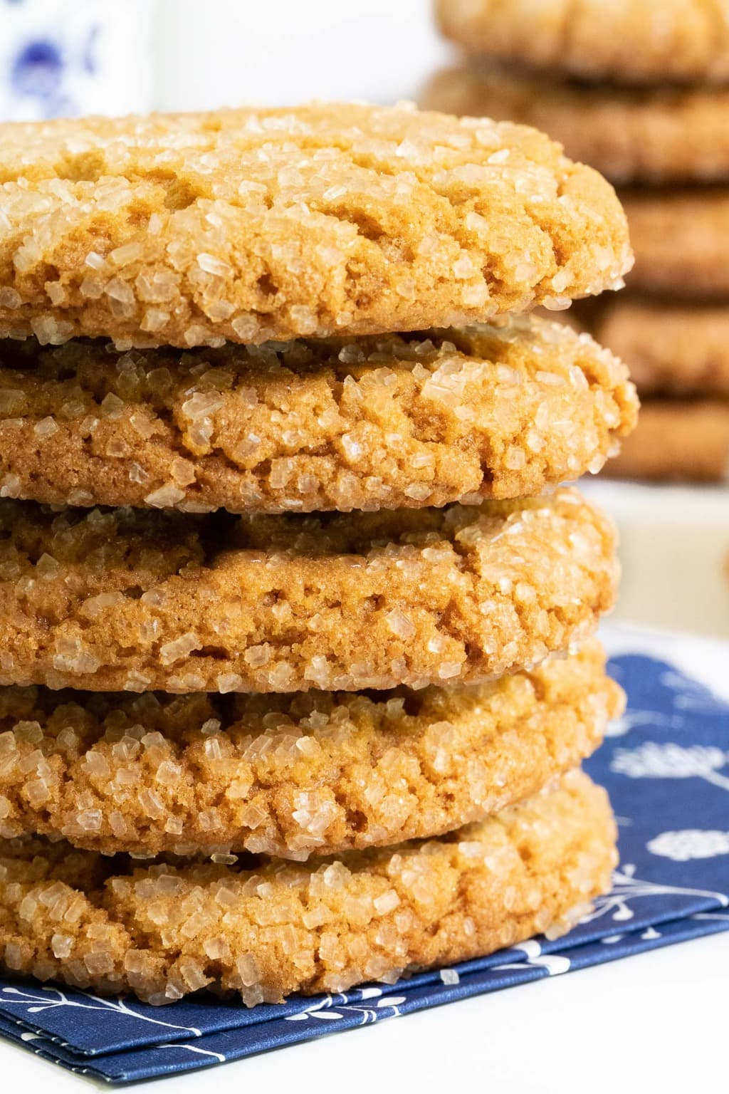 Vertical extreme closeup photo of a stack of Crinkly Crackly Peanut Butter Cookies on a navy and white patterned napkin.