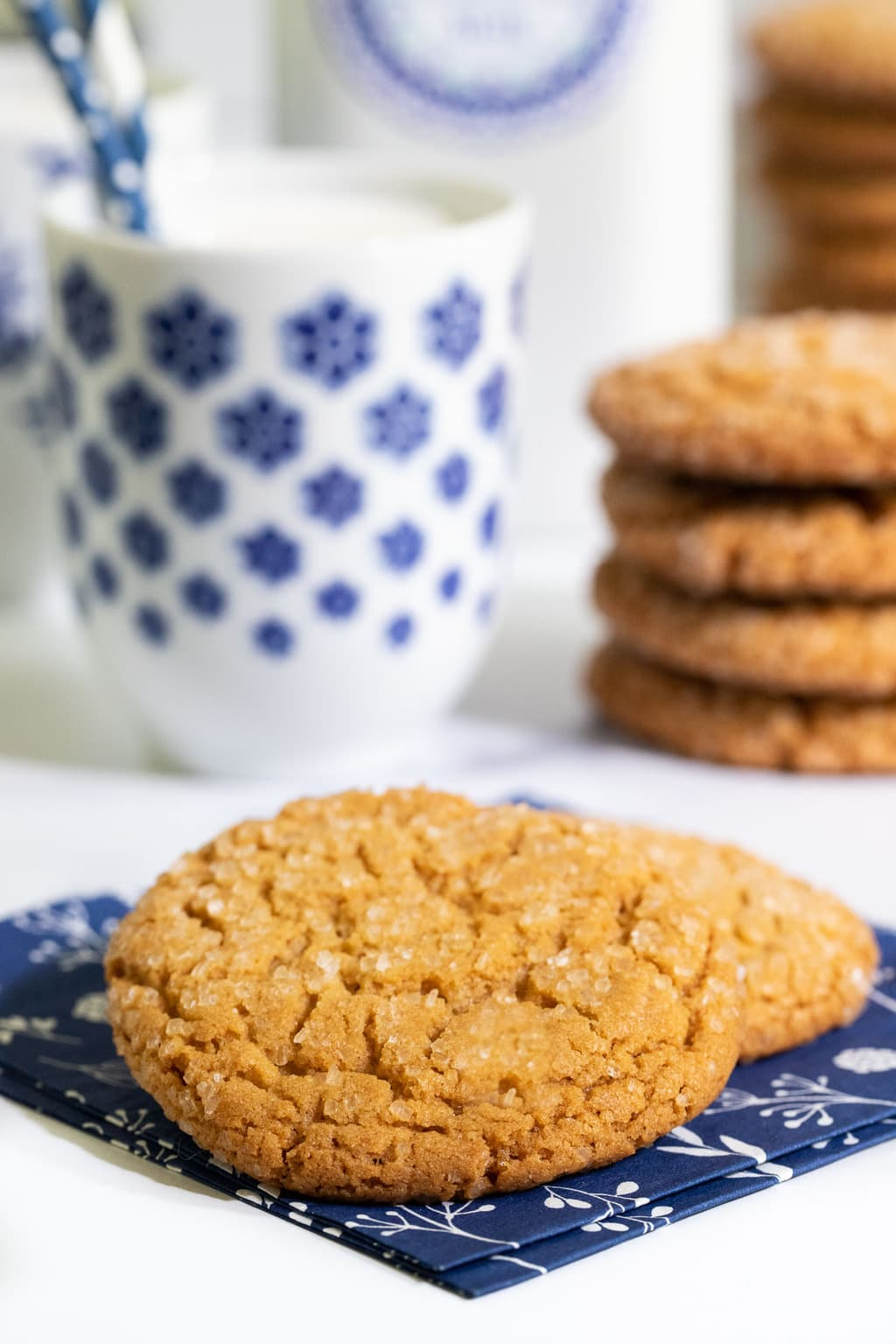 Vertical photo of a batch of Crinkly Crackly Peanut Butter Cookies with cookies in stacks and two on a navy blue napkin.