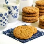 Horizontal photo of a batch of Crinkly Crackly Peanut Butter Cookies with glasses of milk in the background.