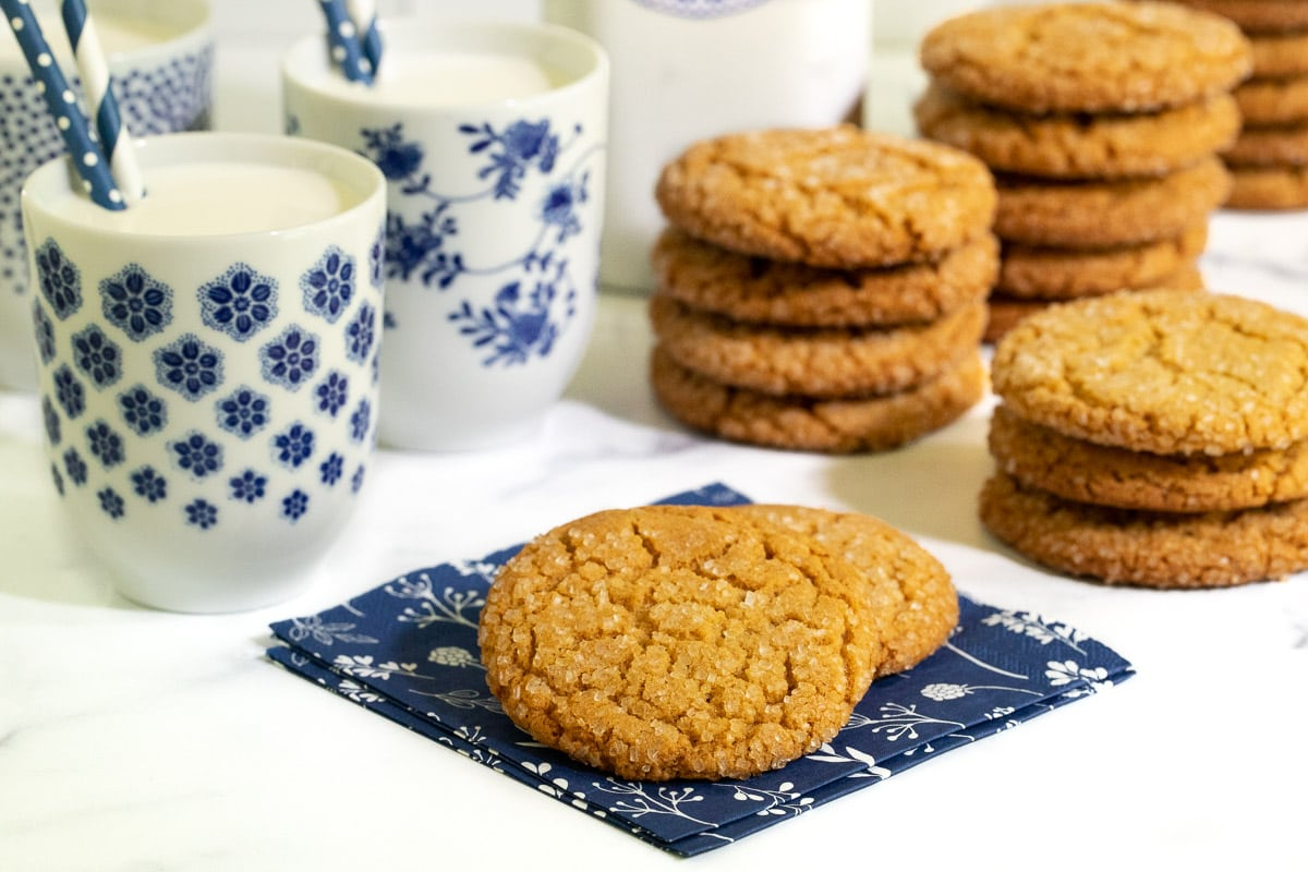 Horizontal photo of a batch of Crinkly Crackly Peanut Butter Cookies on blue napkins and in stacks with cups of milk in the background.