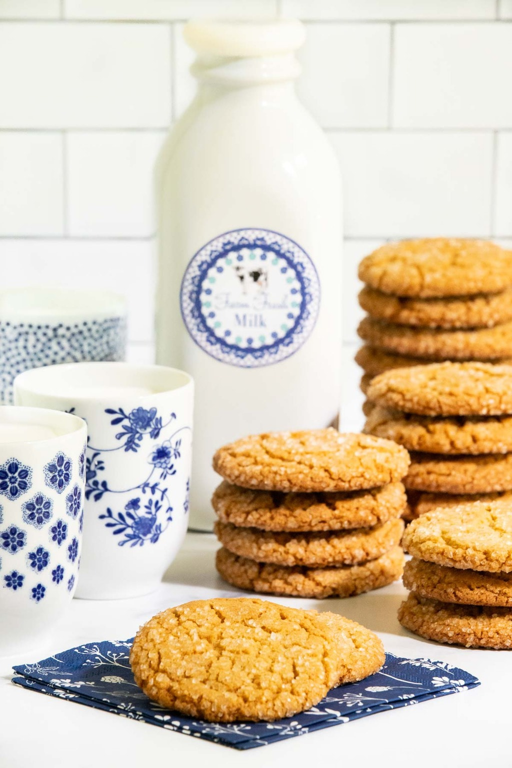 Vertical picture of Crinkly Crackly Peanut Butter cookies stacked with a jar and glasses of milk