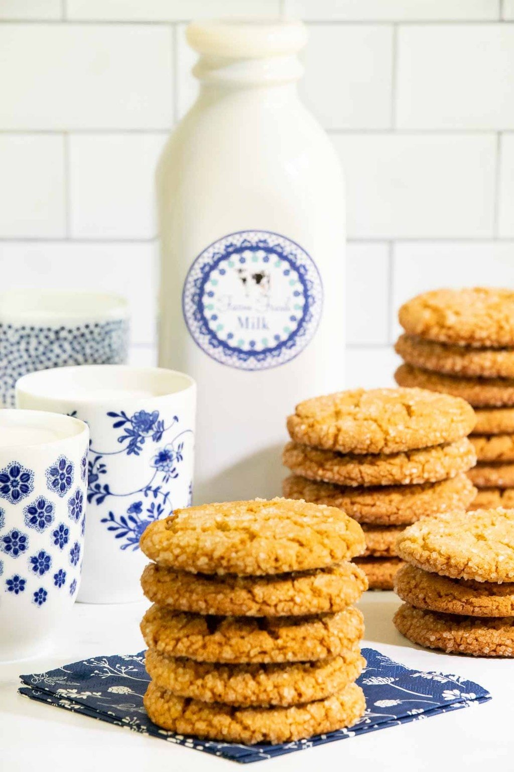 Vertical photo of stacks of Crinkly Crackly Peanut Butter Cookies with a quart and glasses of milk in the background.