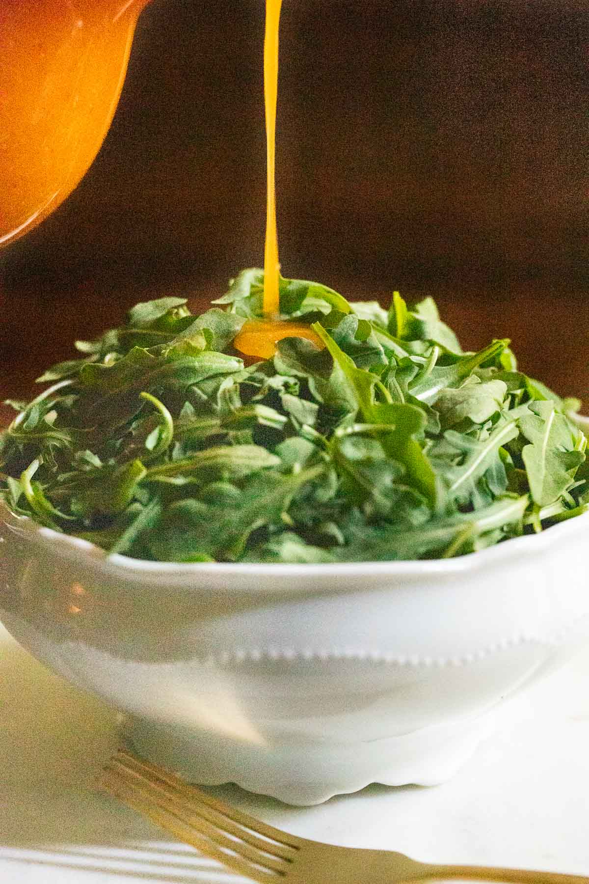 Vertical closeup photo of Red Pepper Jelly Salad Dressing being poured on a baby arugula salad.