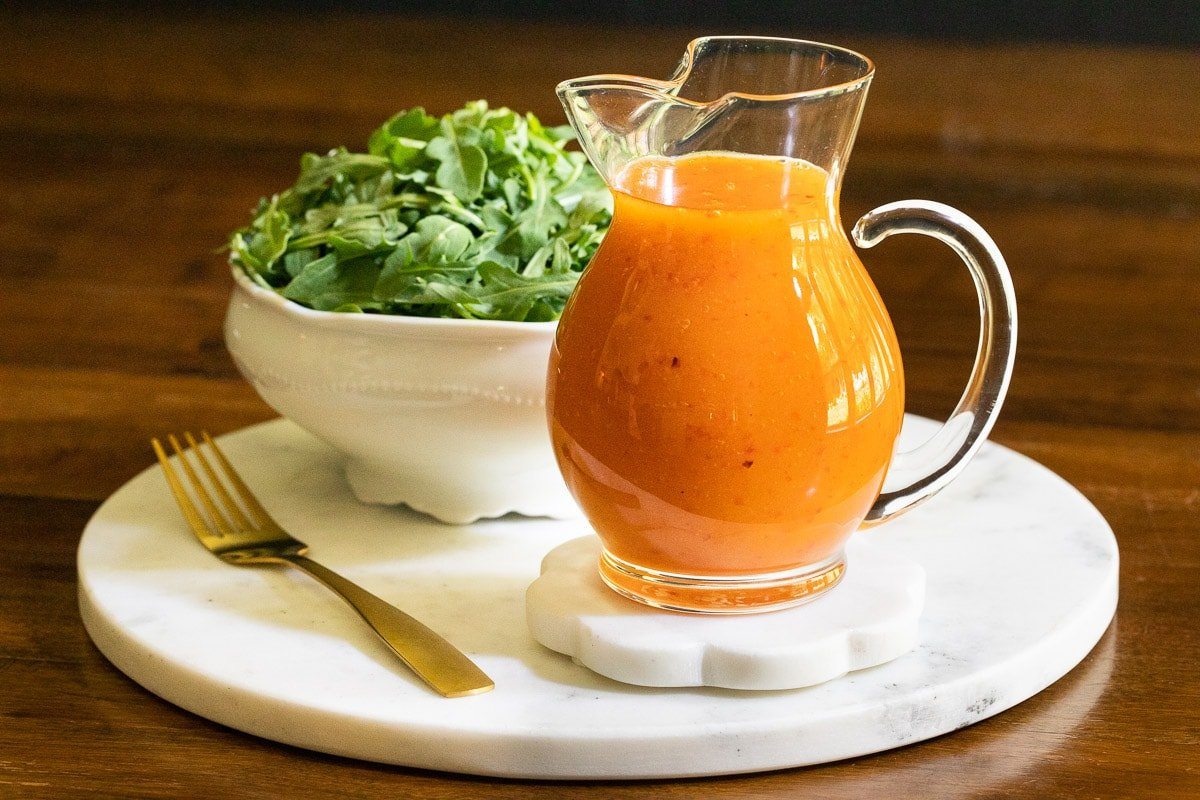 Horizontal closeup photo of a glass pitcher of Red Pepper Jelly Salad Dressing on a round marble surface with a baby arugula salad in the background.