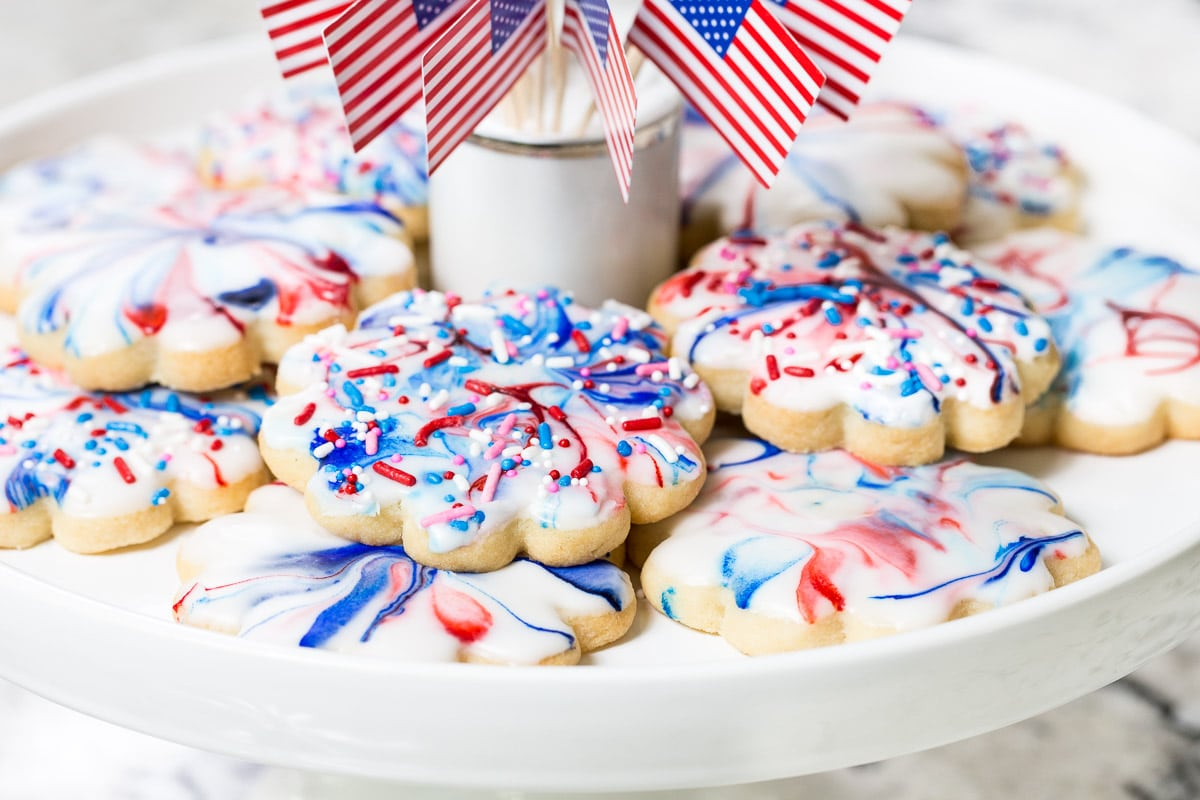 Horizontal closeup photo of a batch of Red, White and Blue Shortbread Cookies decorated with flags on a white pedestal stand.