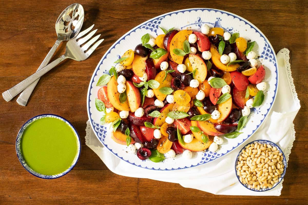 Horizontal overhead photo of a blue and white serving platter filled with Stone Fruit Tomato Caprese Salad on a wood table.